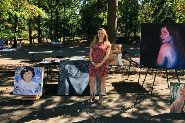 Halle Luttrell in front of some art pieces at her open-air art gallery.